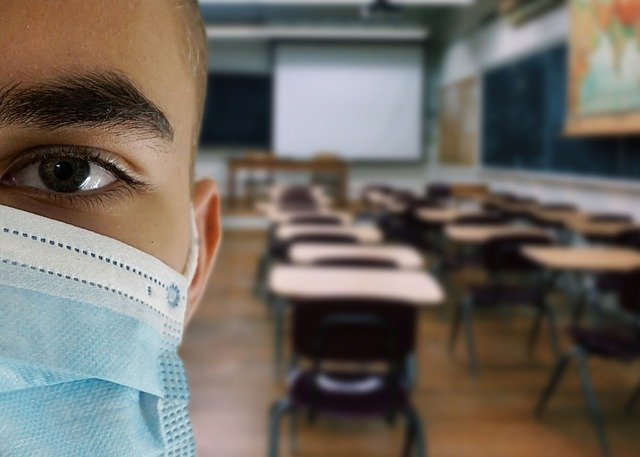 child wearing face mask in empty classroom