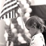 Toddler holding American flag